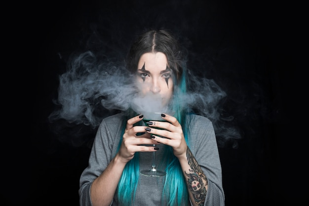 Female holding glass goblet with green liquid and smoke