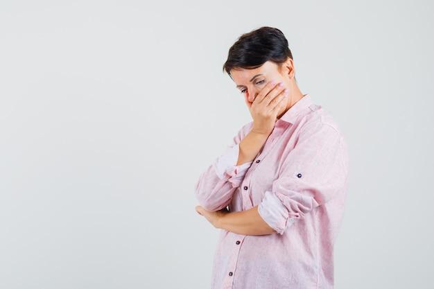 여성 핑크 셔츠에 입에 손을 잡고 화가 찾고. 전면보기.