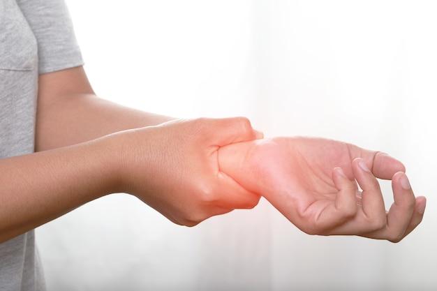 手首の痛み、手首の痛みのスポットに手を保持している女性