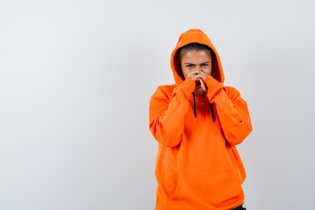 Женщина, держащая руки на лице в оранжевой толстовке с капюшоном и печально выглядящая