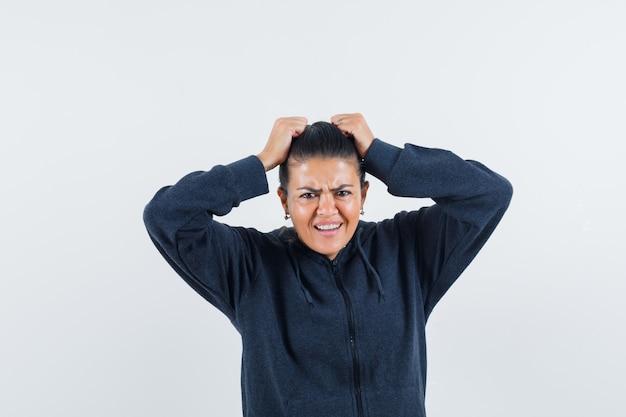 パーカーで頭に手をつないで、緊張している女性、正面図。