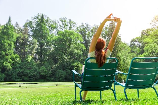 緑の牧草地の肘掛け椅子に座って手を上げて女性。
