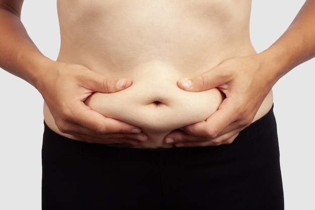Female holding herself for a cellulite belly,obesity in a girl.