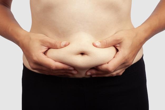 Женщина держится за живот целлюлита, ожирение у девушки.