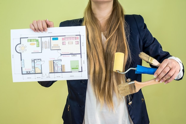 Female holding house plan and work tools