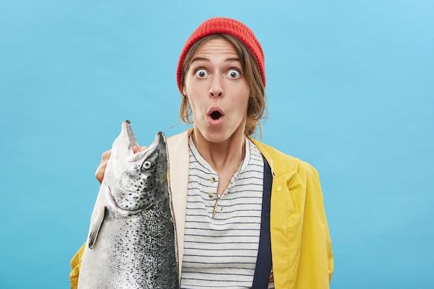 巨大な魚を手で保持している女性