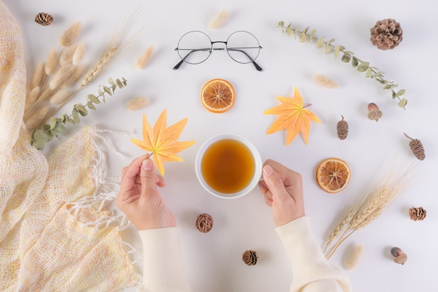Female holding maple leaf and cup of tea over  autumn background.
