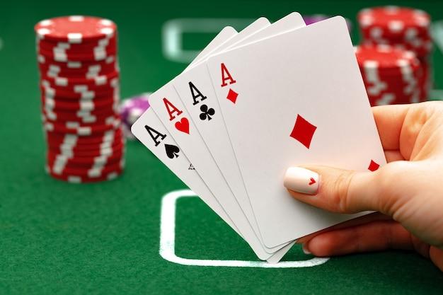 緑のテーブルでポーカーをプレイするトランプを保持している女性
