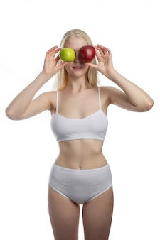 A female holding a red and green apples in different arms isolated on white wall. dental care concept