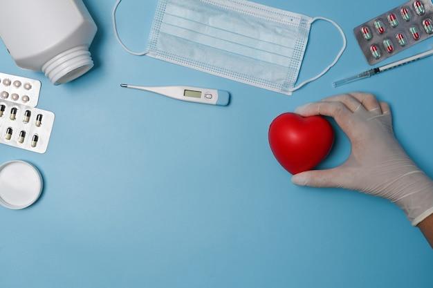 青い背景に赤いハートを保持している女性。心臓病学と保険の概念。