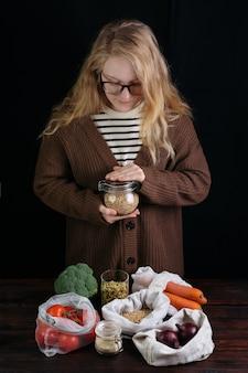 유기농 식품 위에 곡물과 재사용 가능한 은행을 들고 여성