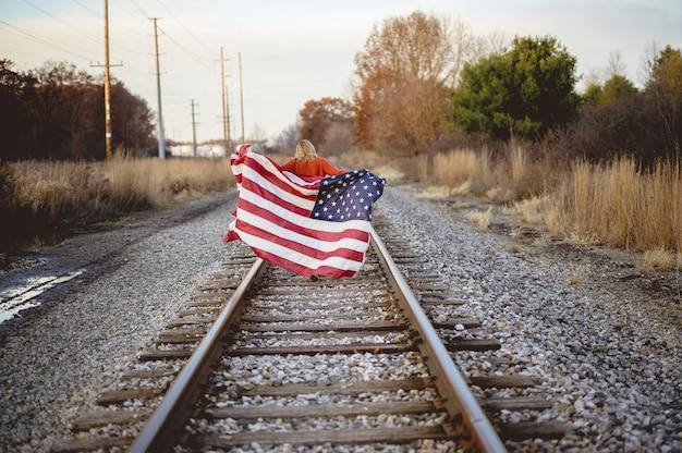 鉄道を歩きながらアメリカの国旗を保持している女性