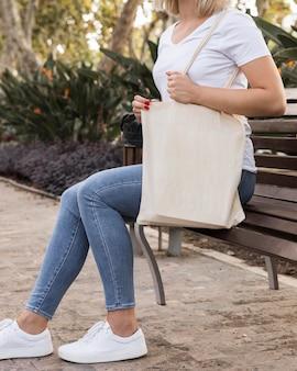 Femmina che tiene una borsa della spesa bianca in un bellissimo parco