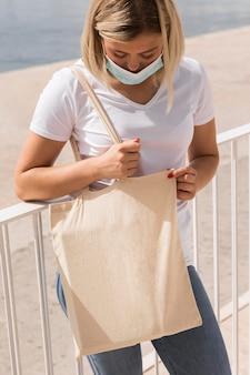 Femmina che tiene una borsa della spesa bianca vicino a un lago