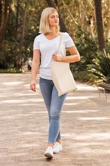 Femmina che tiene una vista lunga del sacchetto della spesa bianco