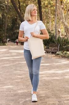 Femmina che tiene un sacchetto della spesa bianco e distoglie lo sguardo