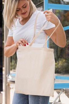 Femmina che tiene un sacchetto della spesa bianco e lo utilizza