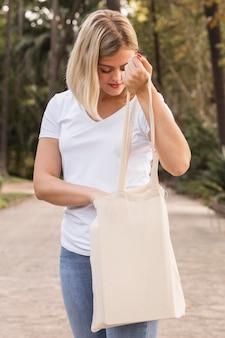 Femmina che tiene una borsa della spesa bianca e camminare