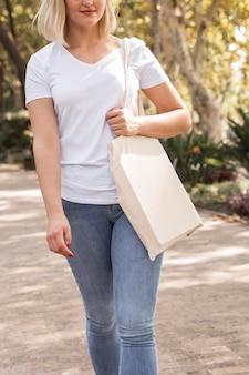 Femmina che tiene una borsa della spesa bianca e indossa una camicia bianca