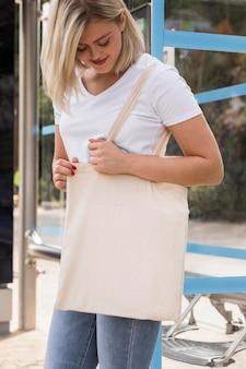 Femmina che tiene una borsa della spesa bianca