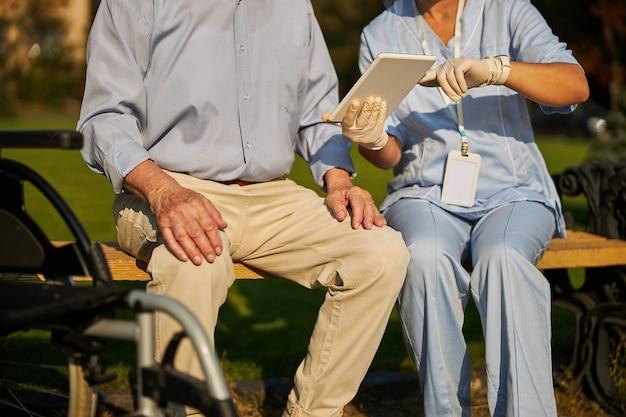 남자 근처에 앉아있는 동안 손에 흰색 태블릿을 들고 여성