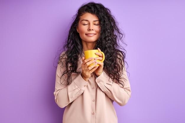 Женщина держит желтую кружку в руках, расслабляясь, пьет кофе или чай по утрам, наслаждаясь закрытыми глазами