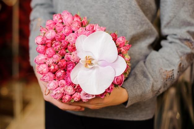 Самка держит букет с множеством маленьких розовых роз и одной большой белой орхидеей