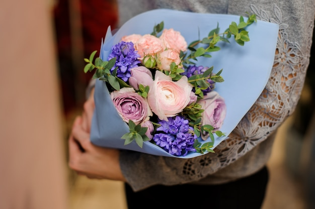 Female holds a bouquet with pink and purple pion-shaped roses, eucalyptus and roses