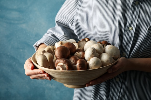 Female holds bowl with different mushrooms on blue, closeup
