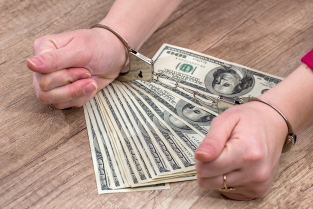 Female holds money dollars in handcuffed