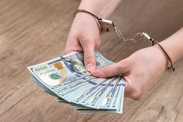 女性は手錠をかけられてお金のドルを保持します