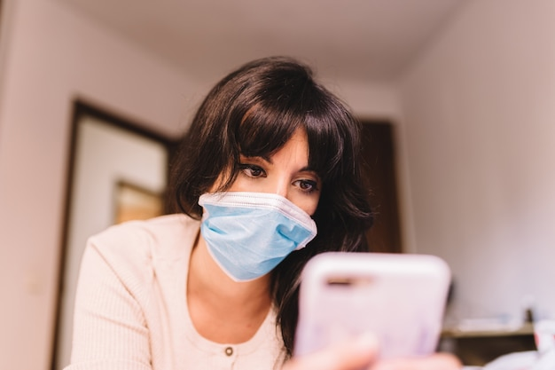 Female at home in breathing medical respiratory mask on her face using mobile phone. pandemic coronavirus, virus covid-19. quarantine, prevent infection concept. focus on her face.