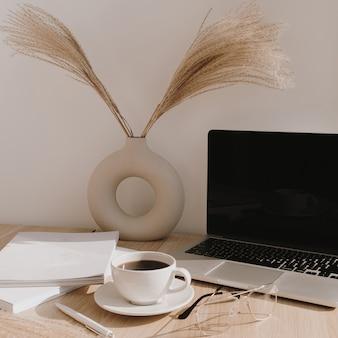 女性のホームオフィスデスクワークスペース。コピースペースのある空白の画面のラップトップコンピューター。コーヒーカップ、ベージュの木製テーブルにスタイリッシュな花瓶のパンパスグラス。