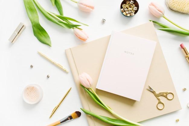 女性のホーム オフィス デスク。ノート、ピンクのチューリップの花、アクセサリーを備えたワークスペース。フラットレイ、トップビュー