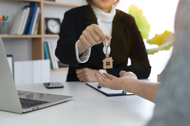 A female home sales agent handed over a keychain to a new homeowner.