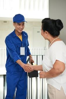 陽気なアジアの配管工と握手する女性の住宅所有者