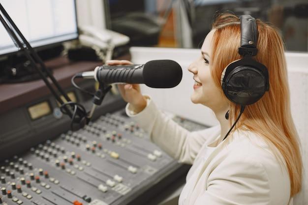 마이크에서 통신하는 여성 호스트. 라디오 스튜디오에서 여자입니다.
