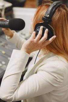 Хозяин женского пола общается по микрофону. женщина в радиостудии.