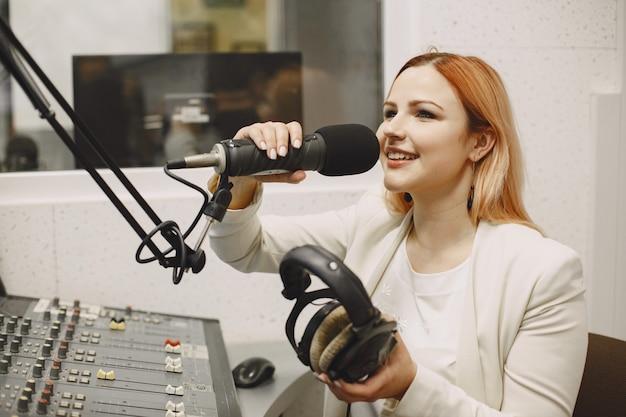 マイクで通信する女性ホスト。ラジオスタジオの女性。