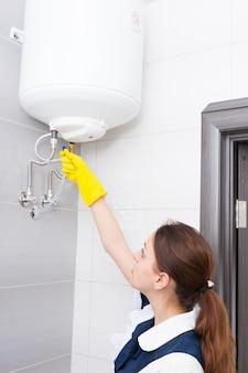 포니테일과 파란색과 흰색 유니폼을 입은 여성 호텔 하녀, 욕실의 천장에 설치된 물 탱크 밸브와 함께 일하는 노란색 고무 장갑