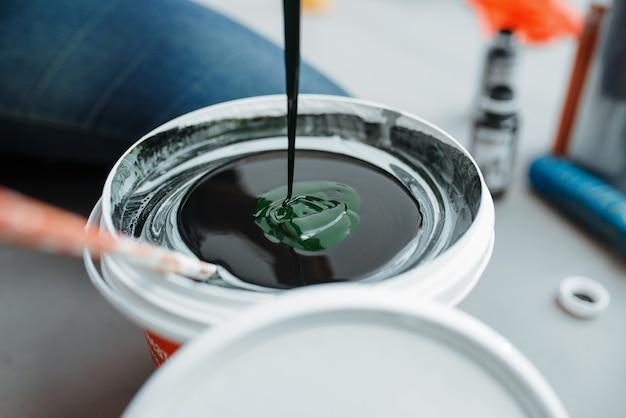 Маляр женского пола смешивает черную и зеленую краски в ведре, крупном плане. ремонт дома, смеющаяся женщина делает ремонт квартиры, ремонт украшения комнаты