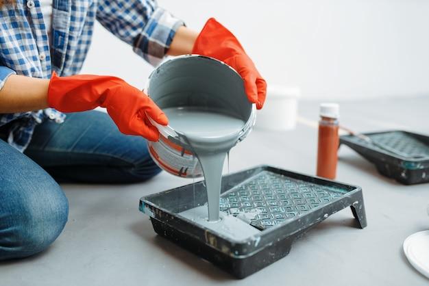 Female house painter prepares for work