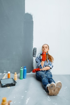 Female house painter with paint roller sitting on the floor after work. home repair, happy woman doing appartment renovation