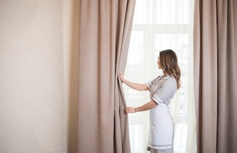 Female housekeeping chambermaid worker with opening curtains of window in room