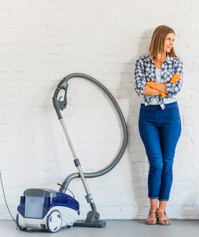 Female housemaid standing near vacuum cleaner in front of brick wall