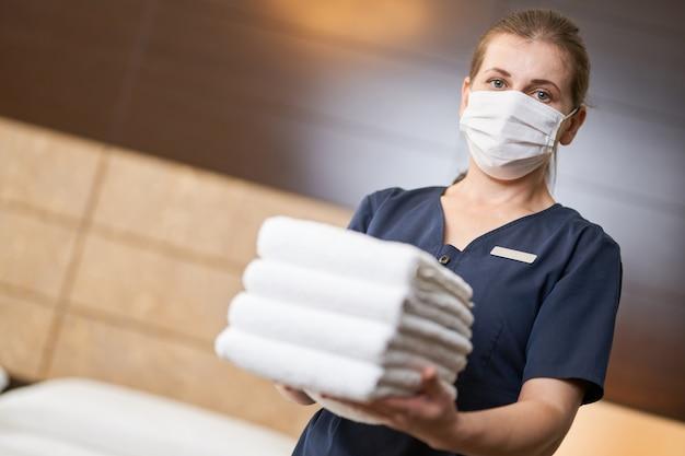 Женщина-горничная стоя со свежими чистыми полотенцами во время уборки в гостиничном номере. концепция гостиничного обслуживания. копировать пространство
