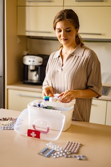 Female housewife checking medicines at domestic first aid kit neatly placing storage organization
