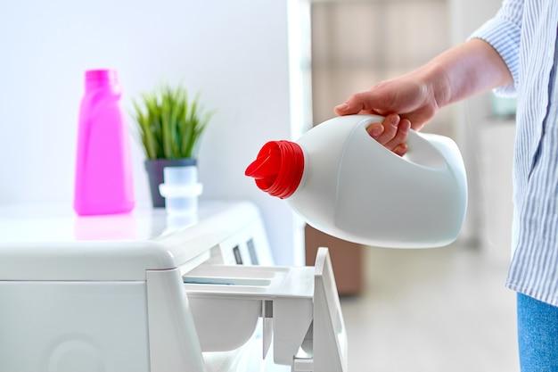 Женщина-домохозяйка наливает гель для смягчения белья в современную стиральную машину