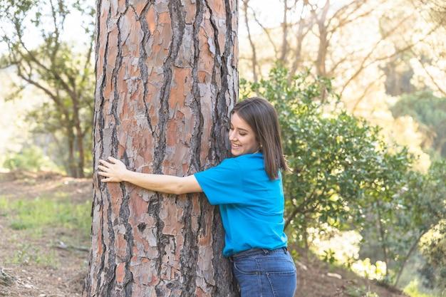 Female hugging green tree in grove