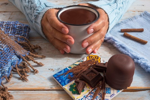 Female human hands holding a chocolate cup creamy and thick wooden table as background with pieces